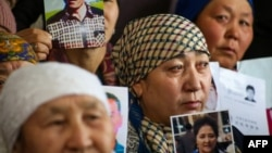 Petitioners with relatives missing or detained in Xinjiang hold up photos of their loved ones in Almaty, Kazakhstan, on January 21.