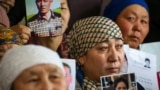 Petitioners with relatives missing or detained in Xinjiang hold up photos of their loved ones during a press event at the office of the Atajurt rights group in Almaty, Kazakhstan, on January 21, 2019.