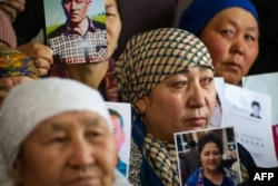 Petitioners with relatives missing or detained in Xinjiang hold up photos of their loved ones during a press event at the office of the Ata Jurt rights group in Almaty, Kazakhstan, on January 21.