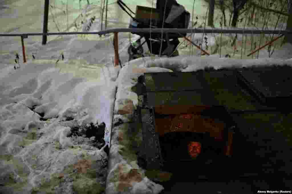 "Yevgeny Korobov, 43, nicknamed ""Korobok"" (Box), sits in a makeshift shelter inside an underground pipe chamber."