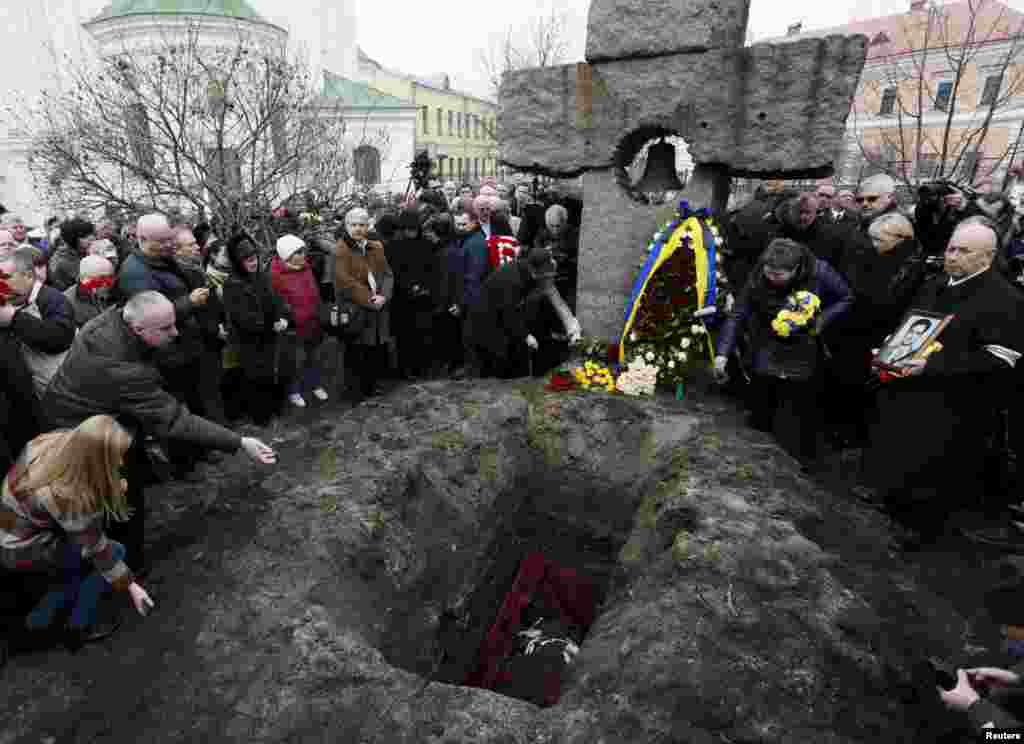 People mourn during the funeral of opposition journalist Georgiy Gongadze, who was killed in 2000, during a funeral ceremony near the Church of Mykola Naberezhny in Kyiv, Ukraine. Gongadze, a dogged investigative journalist who exposed high-level political corruption, was kidnapped in September 2000. His headless body was found that November in a forest outside the capital. His body had been kept in a morgue ever since. Reuters/Valentyn Ogirenko)