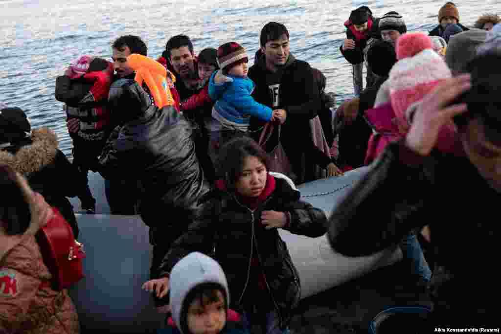 Afganistanski migranti izlaze iz čamca na plaži u blizini sela Skala Sikamias na grčkom ostrvu Lesbos nakon što su prešli dio Egejskog mora iz Turske.