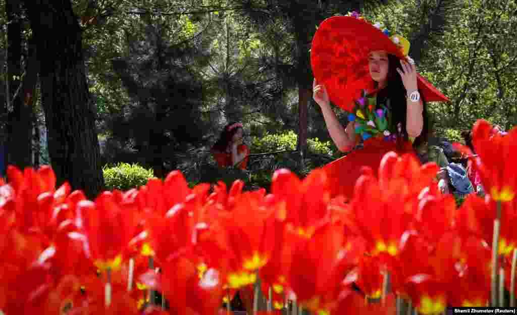 """Фестивальге қатысушылардың бірі """"Президент Назарбаев"""" қызғалдақтарының жанында тұр.Бұл қызғалдақтар Алматыдағы Орталық демалыс паркіне отырғызылған."""
