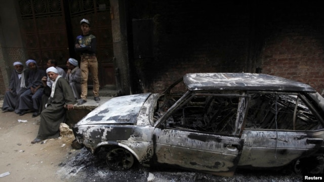 Egyptians sit near a burnt car after clashes between Muslims and Christians in Khusus, El-Kalubia governorate, about 25 kilometers northeast of Cairo, on April 6.
