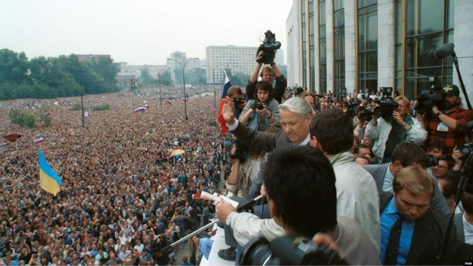 """Виступ президента Росії Бориса Єльцина на мітингу в Москві, 20 серпня, 1991 року. На мітингу майорять і українські прапори, на передньому плані – синьо-жовтий прапор, а на задньому – червоно-чорний. Українці брали активну участь в масових акціях у Москві, які, в кінцевому результаті, призвели до розпаду радянської імперії. Зокрема, із 1989 року в Москві діяла організація з назвою """"ОУН-РУХ"""""""