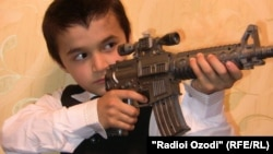 Arxiv foto: Tacikistanda oyuncaq silahı ilə oynayan məktəbli. 29 avqust 2011