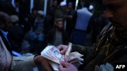 FILE: Afghan money changers count banknotes at the currency exchange Sarayee Shahzada market in Kabul.