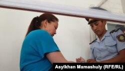 Сотрудник сил безопасности Казахстана надевает наручники на Сайрагуль Сауытбай, этническую казашку из Китая, обвиняемую казахстанским судом в незаконном пересечении границы. Жаркент, 13 июля 2018 года.