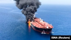 Smoke rises from an oil tanker in the Gulf of Oman after an explosion hit the vessel.