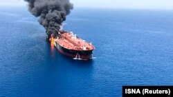 One of the two oil tankers is seen on fire in the sea off Oman on June 13.