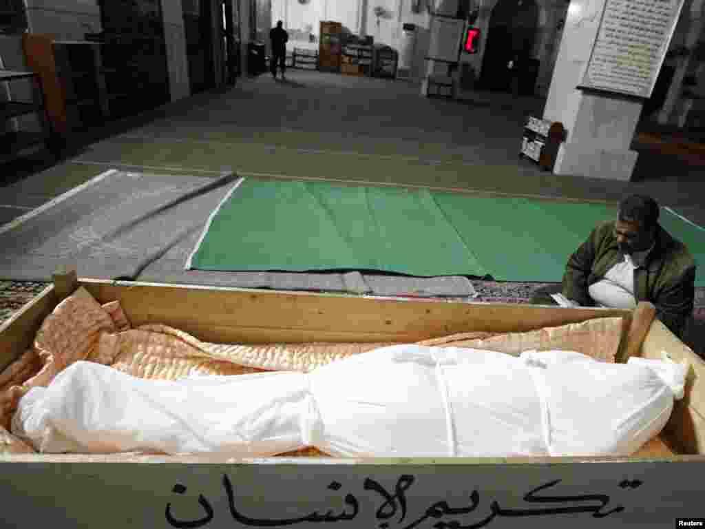 Брат погибшего футбольного фаната читают молитву в мечети.