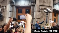 Protesters rally against threats to journalists in Serbia in front of government headquarters in Belgrade on October 16.