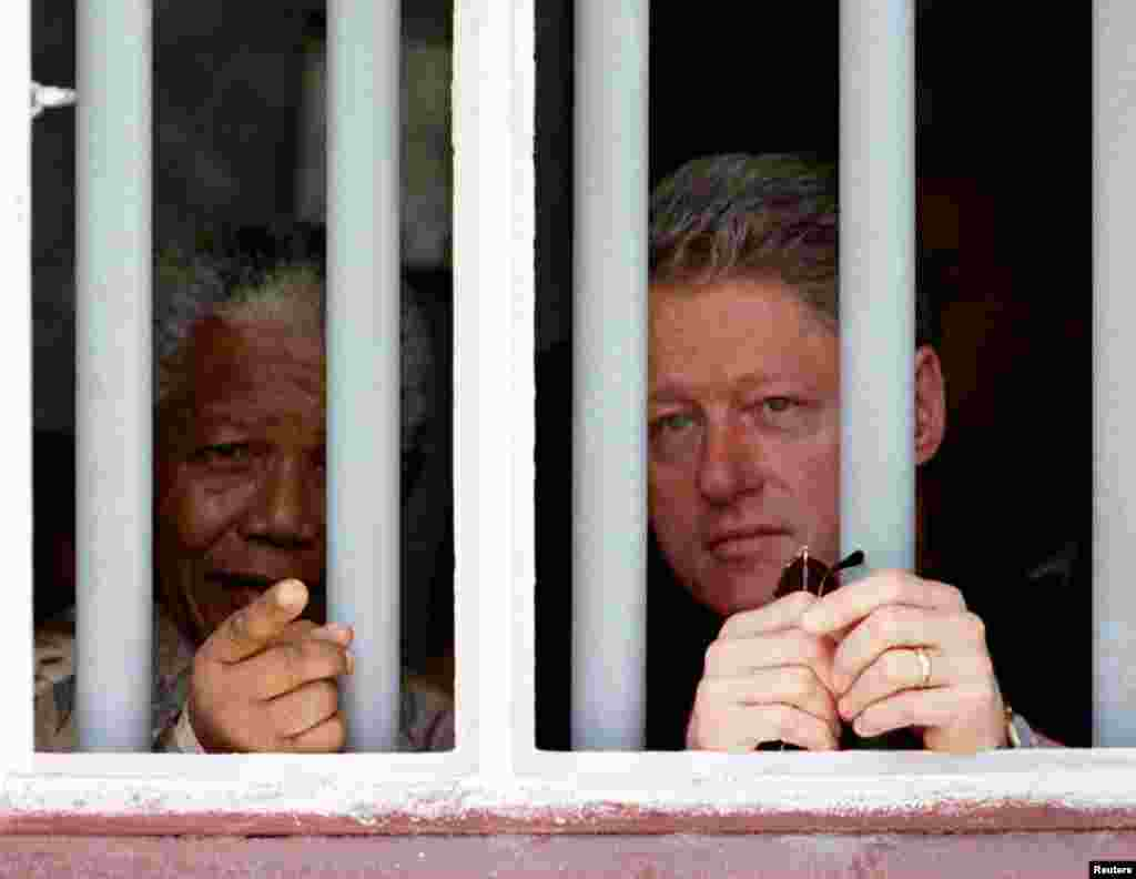 Президент США Билл Клинтон (справа) и Нельсон Мандела смотрят из-за решетки камеры в тюрьме Роббен-Айленда в марте 1998 года.