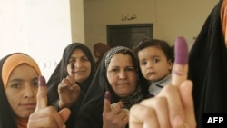 Iraqi women show their ink-stained fingers after casting their votes at a polling station in Baqubah.