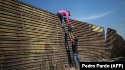 Мексиканың Педро Пардо қаласындағы шекара бойына тұрғызылған дуалдан өтіп бара жатқан мигранттар.