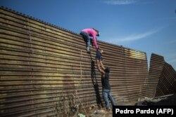 Мигранты пытаются преодолеть пограничную стену на американо-мексиканской границе