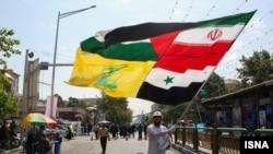 بر افراشتن بیرقی مرک از پرچمهای ایران، فلسطین، سوریه و حزبالله در مراسم روز قدس در تهران در سال ۹۵
