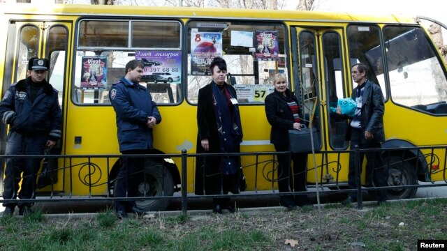 Election commission officials accompanied by the police wait for a bus to deliver ballots for the upcoming referendum in the Crimean capital Simferopol.