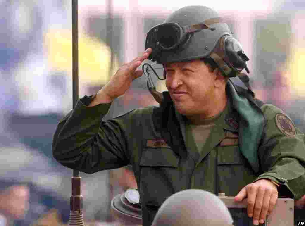 Chavez salutes from atop an armored vehicle during Army Day in Caracas on June 24, 2005.