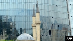 Azerbaijan -- A mosque is seen in front of the Flame Towers in Baku, 08Jun2011