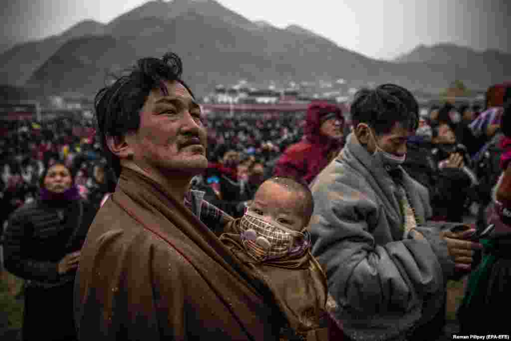 An ethnic Tibetan man holding a child looks at a huge sacred painting on cloth depicting Buddha during a prayer festival at Labrang Monastery in Xiahe, Gansu Province. (epa-EFE/Roman Pilipey)