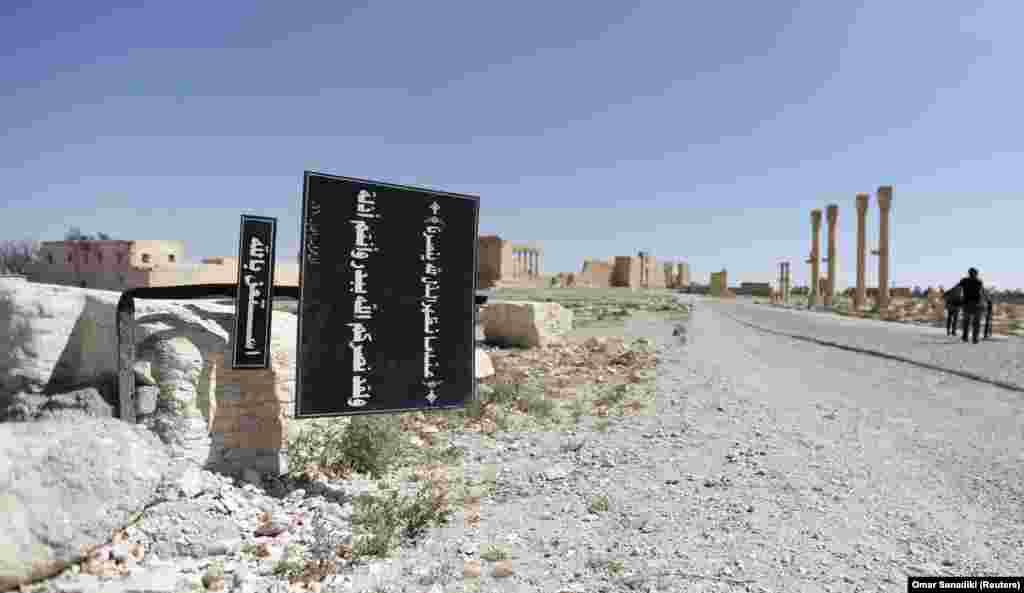 A billboard with Koranic verses is seen in the ancient city of Palmyra. Syrian and Russian forces retook the city from IS in March 2016, but the group seized the historic capital again in December. Many of the site's most treasured monuments have now been destroyed.