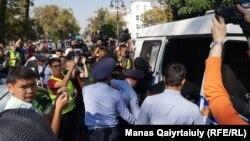 Журналисты снимают то, как полицейские заталкивают в полицейский микроавтобус задержанного участника мирной акции протеста. Алматы, 21 сентября 2019 года.