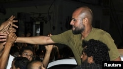 Լիբիա -- Մուամար Քադաֆիի որդին եւ իշխանության ժառանգորդը` Սաիֆ ալ-Իսլամը ողջագուրվում է աջակիցների հետ, Տրիպոլի, 23-ը օգոստոսի, 2011թ.