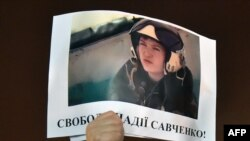 "A demonstrator in Kyiv holds aloft a picture of the Ukrainian army officer captured by pro-Russian insurgents and taken to Russia, Nadia Savchenko, with the words ""Free Nadia Savchenko."""