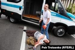 Нанесшая себе порезы женщина лежит рядом с полицейской машиной во время массовых задержаний в Алматы. 10 июня 2019 года.