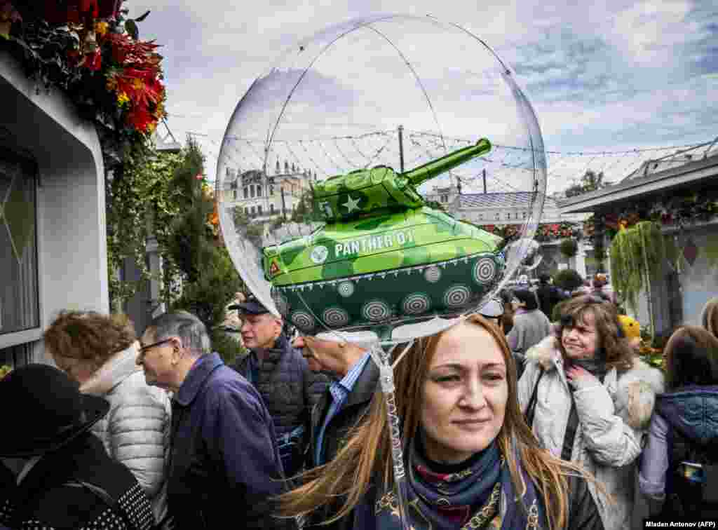 A woman carries a children's balloon with a tank inside during an autumn festival held in central Moscow. (AFP/Mladen Antonov)