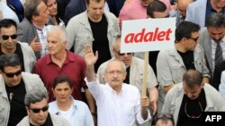 Turkish opposition leader Kemal Kilicdaroglu marches with a sign reading 'Justice.'