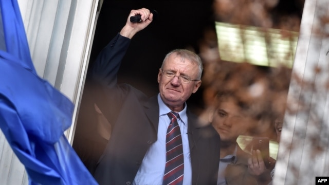 Serbian nationalist leader Vojislav Seselj waves at supporters after arriving at his Serbian Radical Party (SRS) headquarters in Zemun, near Belgrade, on November 12.