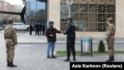 An Azeri law enforcement officer checks a resident's permission to leave home received in a text message, after the authorities imposed restrictions on movement to prevent the spread of the coronavirus disease in Baku.