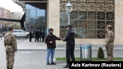 Силовики проверяют у жителя разрешение на выход из дома после введенного властями ограничения на передвижение на улице во время вспышки коронавируса. Баку, 5 апреля 2020 года.