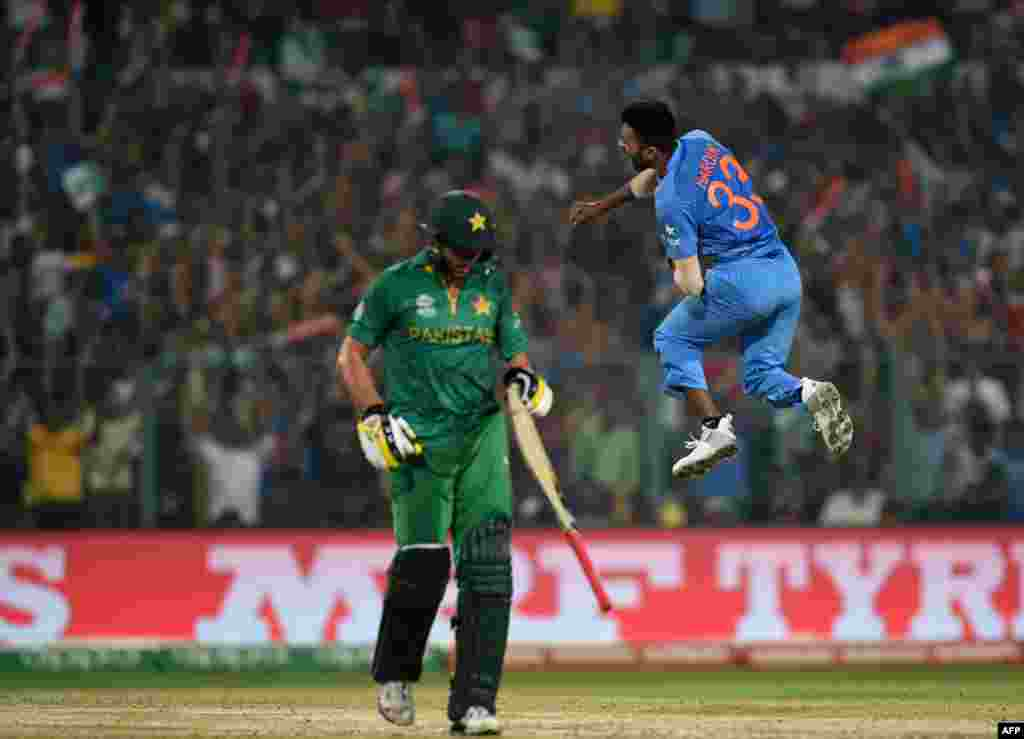 India's Hardik Pandya, right, celebrates after his dismissal of Pakistan captain Shahid Afridi, left, at the Eden Gardens Cricket Stadium in Kolkata on March 19.