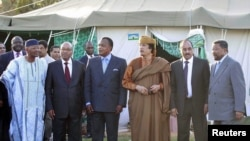 Muammar Qaddafi (third from right) and a delegation from the African Union stand outside a tent erected at Qaddafi's residence in Tripoli on April 10.