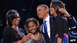 Президент США Барак Обама вместе с дочерьми и женой празднуют победу на выборах. Чикаго, 7 ноября 2012 года.