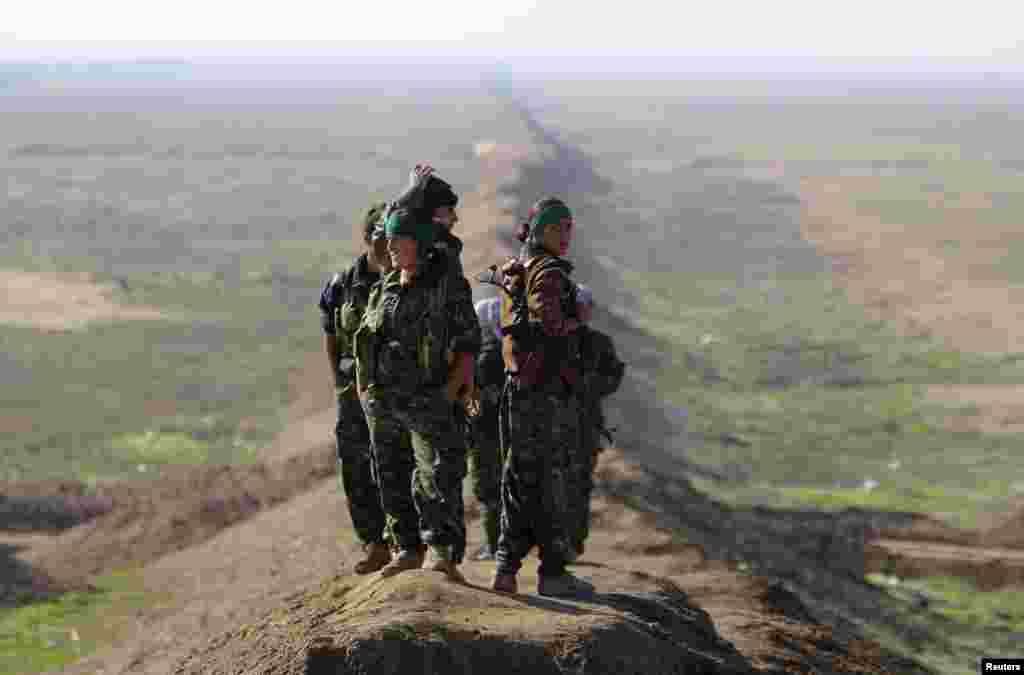 Female fighters with the Kurdish People's Protection Units (YPG) stand near the border between Syria and Iraq, close to the Iraqi town of Snoun. (Reuters)