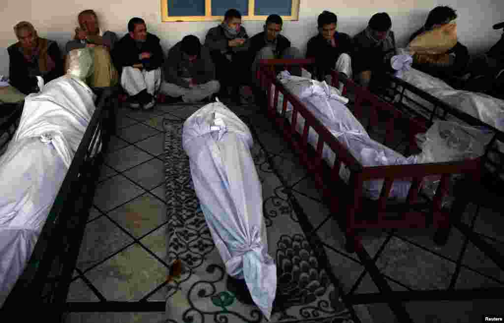 People gather around victims during a funeral service at a Quetta mosque.