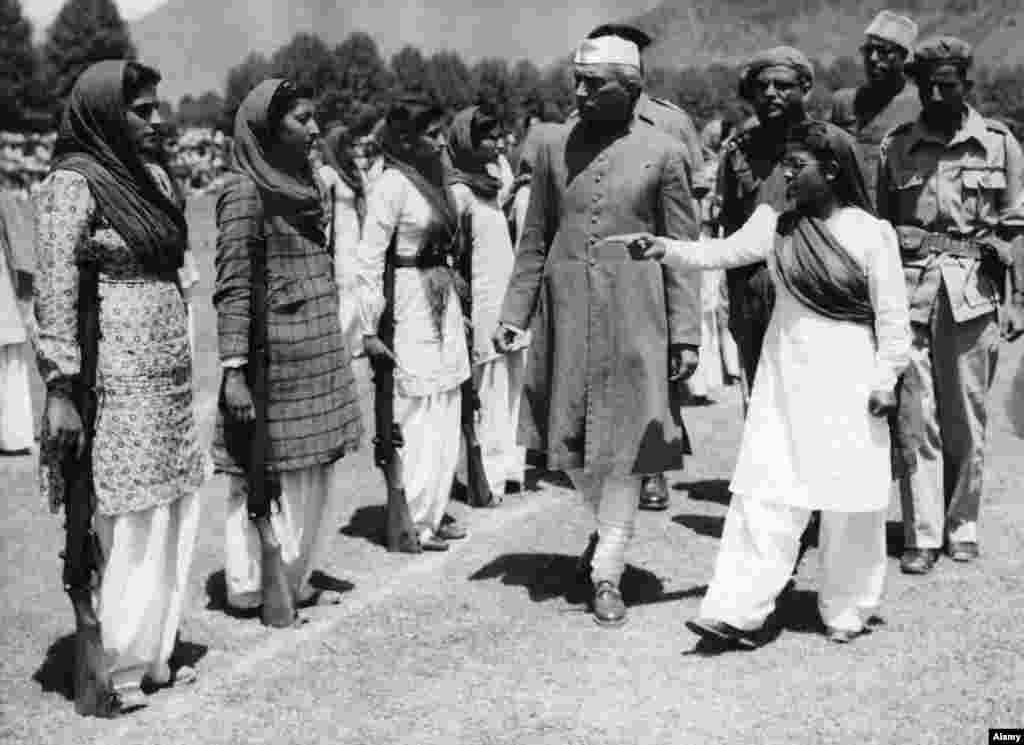 Инспекция на жени войници от страна на министър-председателя на Индия Джавахарлал Неру в Кашмир през 1947 г. Има множество твърдения, че Махараджа Сингх е напуснал региона преди да подпише присъединяването и съответно не е имал правото да обяви Джаму и Кашмир за част от Индия.