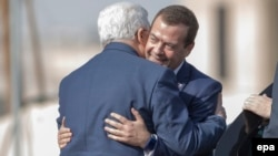 Palestinian leader Mahmud Abbas (left) embraces Russian Prime Minister Dmitry Medvedev during a ceremony in the West Bank city of Jericho on November 11.
