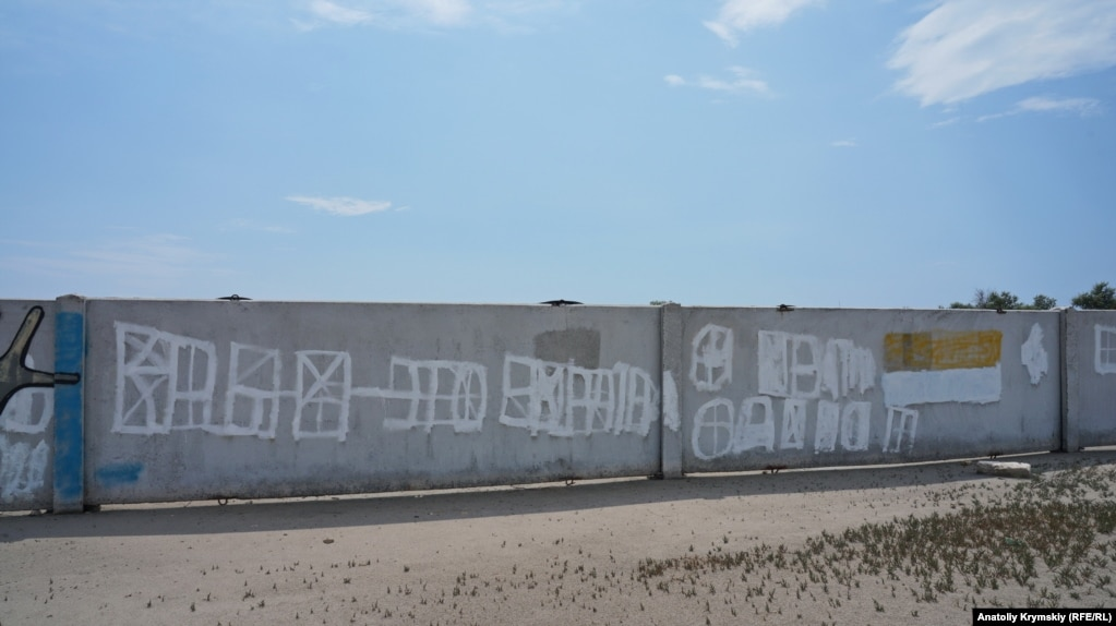 В зачеркнутой надписи на заборе кемпинга все же проглядываются изначальные слова.