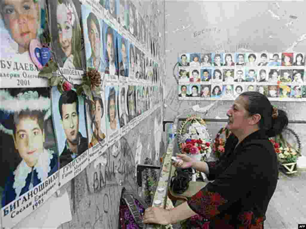 A woman looks at photos of the Beslan victims while visiting the ruined school in May (AFP) - Videos released last month appear to substantiate this claim. One shows Russian experts at the scene in the days that followed the massacre agreeing the explosion that launched the battle came from outside.