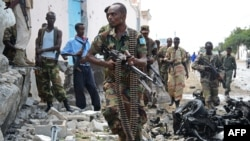 Somali National Government soldiers at the scene after Al-Qaeda-linked Shebab insurgents blasted their way into the UN compound in Mogadishu on June 19.