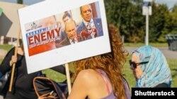 """Участники акции протеста перед зданием Европарламента против авиаударов по сирийскому городу Дума, на плакате написано: """"Россия — враг"""". Страсбург, 20 августа 2015 года."""