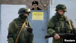 Ukrain esgeri rus harbylarydygy çaklanylýan adamlara nazar aýlaýar. Simferopol. 3-nji mart, 2014 ý.