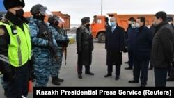 Президент Казахстана Касым-Жомарт Токаев в сопровождении чиновников на блокпосту на выезде из Нур-Султана во время действия режима ЧП. 19 марта 2020 года.