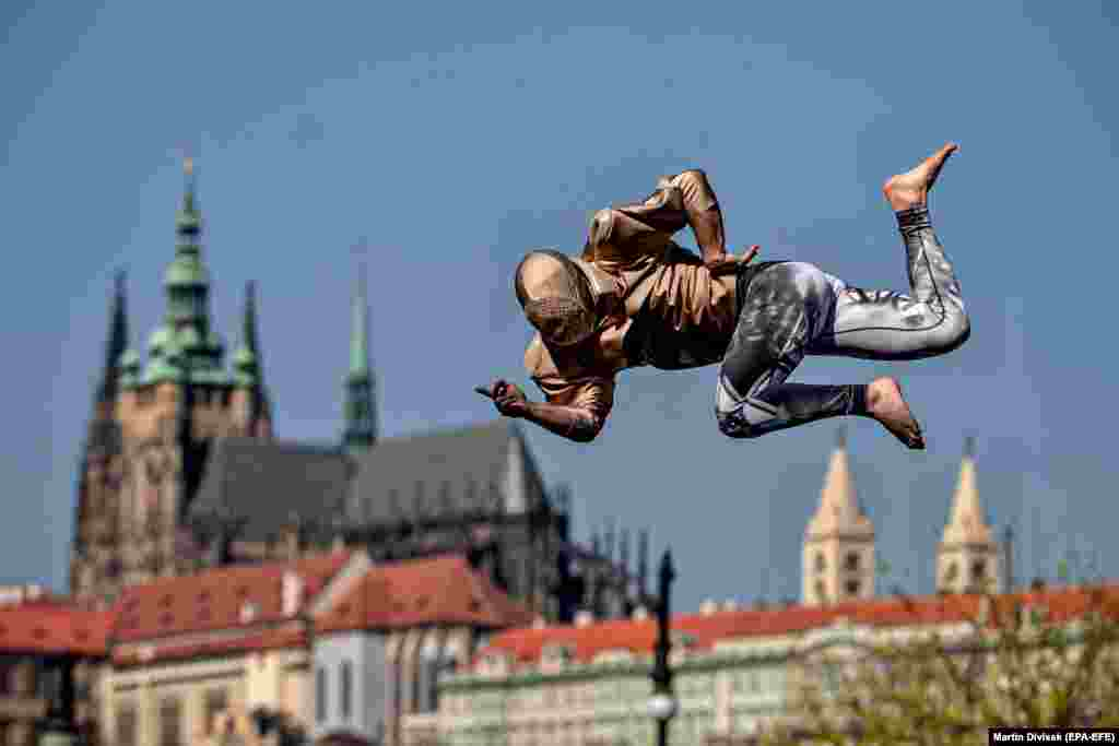 A member of the artistic group Cirk La Putyka performs on a trampoline in Prague on April 9. The aim of Cirk La Putyka events in the streets of the Czech capital is to get live art back to people during the coronavirus lockdown. (epa-EFE/Martin Divisek)