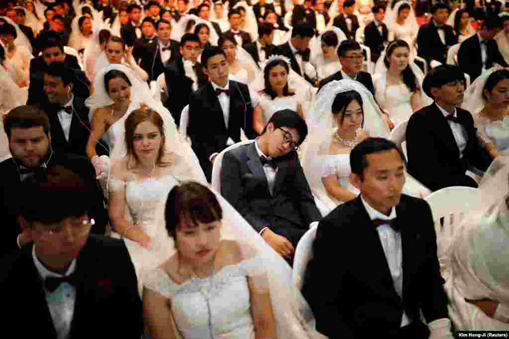 A groom naps as newlywed couples attend a mass wedding ceremony of the Unification Church at Cheongshim Peace World Center in Gapyeong, South Korea. (Reuters/Kim Hong-Ji)